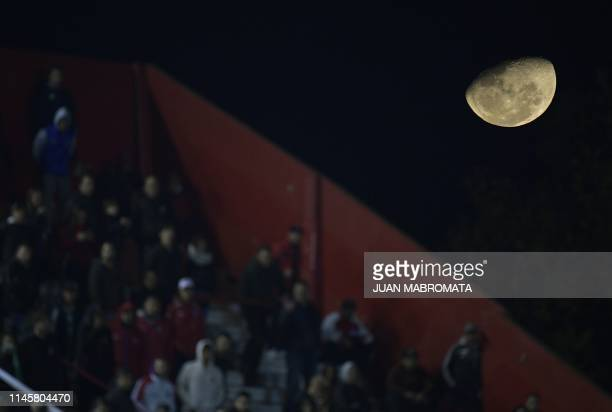 The moon is seen as fans of Argentine team Argentinos Juniors watch the Copa Sudamericana football match against Colombia's Deportes Tolima at the...
