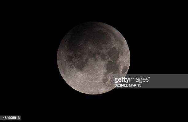 The moon is seen as it emerges from a total lunar eclipse from the Spanish Canary island of Tenerife on April 15 2014 People in most of north and...