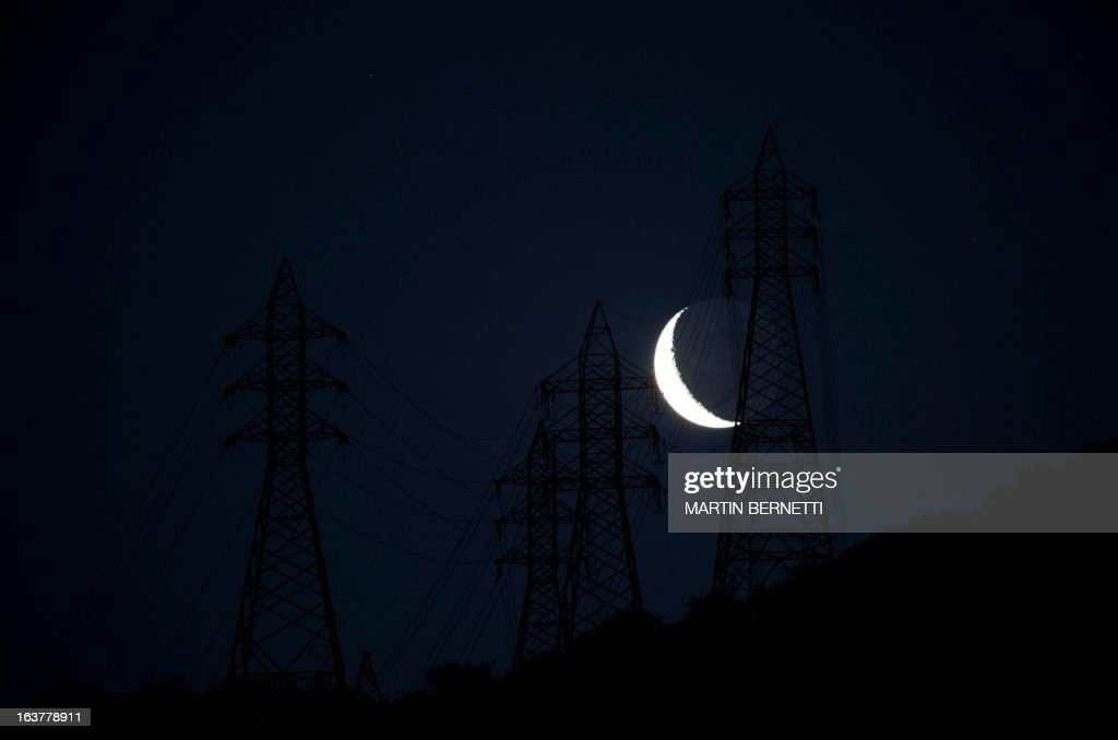 The moon is seen behind electricity pylons as it rises over Santiago, Chile, on March 15, 2013.