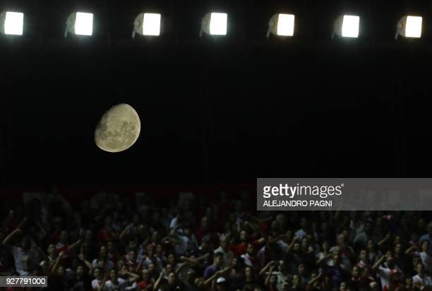 The moon is seen behind supporters of Argentinos Juniors during the Argentina First Division Superliga football match against Boca Juniors at the...