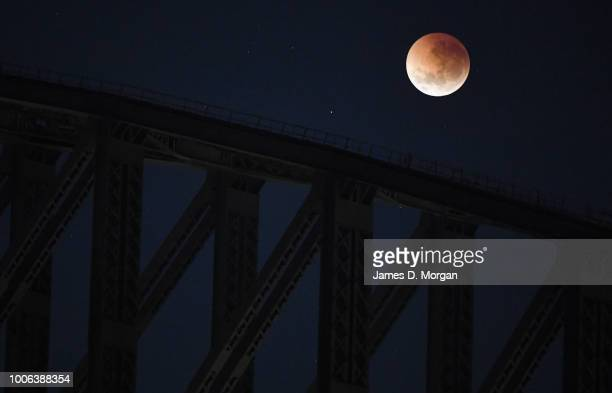 The moon is seen behind the Harbour Bridge turning red during a total lunar eclipse on July 28 2018 in Sydney Australia The lunar eclipse was the...