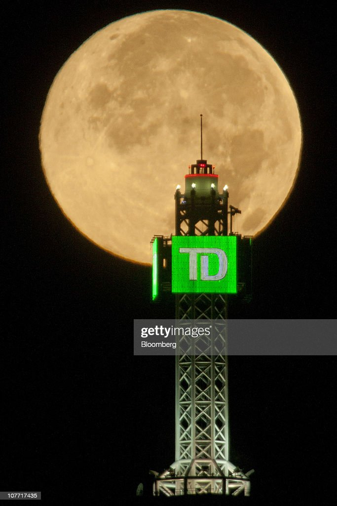 The Moon is seen beyond a Toronto-Dominion Bank (TD) logo displayed atop the TD Canada Trust Tower in the financial district of Toronto, Ontario, Canada, on Sept. 4, 2009. Toronto-Dominion Bank agreed to buy Chrysler Financial Corp. from Cerberus Capital Management LP for $6.3 billion in cash, adding an auto-finance company in its second-largest acquisition. Photographer: Norm Betts/Bloomberg via Getty Images