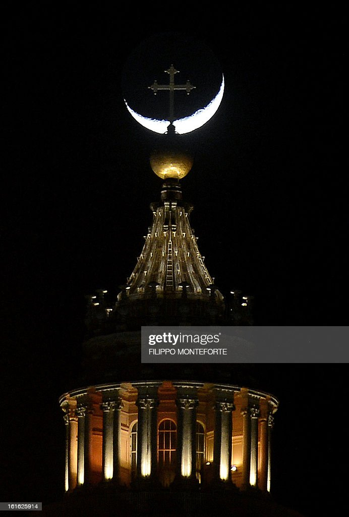 The moon is seen by the cross on the top of Saint Peter's dome at the Vatican on February 13, 2013. Pope Benedict XVI made his first public appearance today since his shock resignation announcement, asking thousands of cheering pilgrims at the Vatican to 'keep praying for me'.