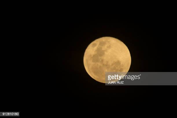 The moon is seen during a lunar eclipse referred to as the 'super blue blood moon' from Quito on January 31 2018 Skywatchers witnessed a rare lunar...