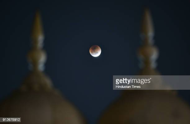 The moon is seen during a lunar eclipse seen at Jama Masjid on January 31 2018 in New Delhi India In rare celestial event a supermoon blue moon and...