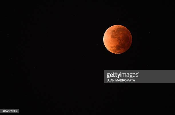 The moon is seen during a total eclipse in Buenos Aires on April 15 2014 The entire event was to be visible from North and South America but sky...