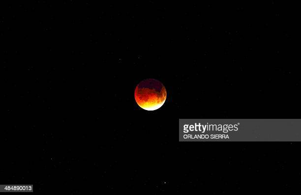 The moon is seen during the early stages of a total lunar eclipse over the Honduras city of Tegucigalpa early on April 15 2014 The entire event was...
