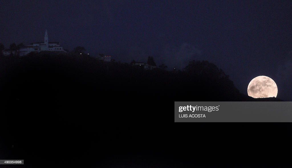 The moon is seen near to Moserrate mountain in Bogota on September 27 2015. This Sunday, September 27 will happen a total lunar eclipse while super moon, a natural phenomenon that will be repeated in 2033. AFP PHOTO/Luis Acosta /