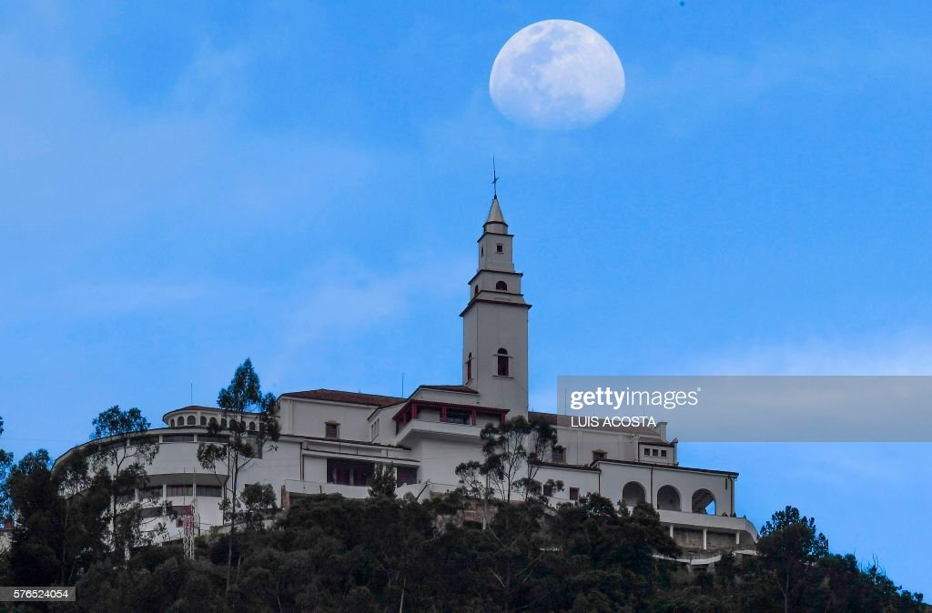 The moon is seen over the Monserrate Mountain in Bogota on July 15, 2016. / AFP PHOTO / Luis Acosta