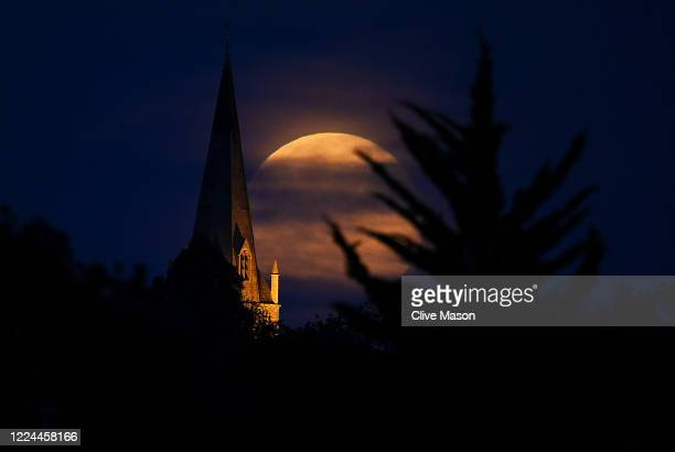 The moon is seen rising above the village of Brixworth on May 07 2020 in Brixworth England A supermoon occurs when the moon reaches its closest...