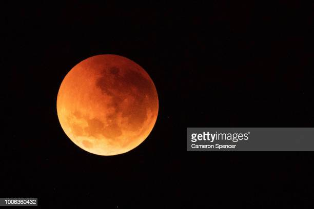 The moon is seen turning red over the Sydney skyline during a total lunar eclipse on July 28 2018 in Sydney Australia The lunar eclipse was the...