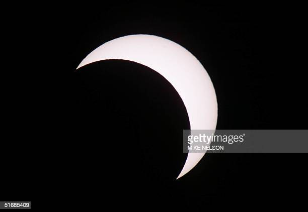 The moon moves in front of the sun as it reaches its height at 70 percent during a partial solar eclipse visible from Mexico to the western United...