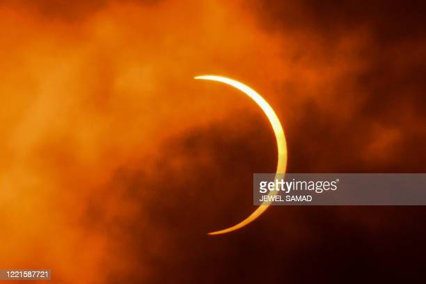 TOPSHOT The moon moves in front of the sun during an annular solar eclipse as seen through clouds from New Delhi on June 21 2020