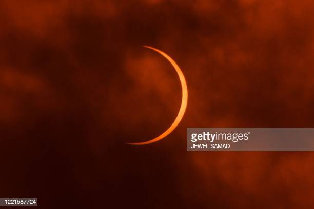 The moon moves in front of the sun during an annular solar eclipse as seen through clouds from New Delhi on June 21 2020