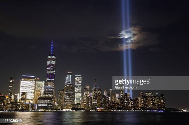 The moon passes through the annual Tribute in Light illuminated on the skyline of lower Manhattan on the 18th anniversary of the 9/11 attacks in New...