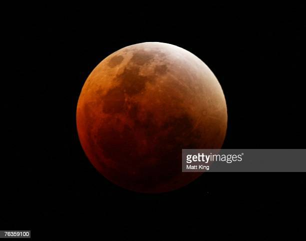 The moon passes through the earth's shadow to appear red during a total lunar eclipse August 28 2007 in Sydney Australia The next total lunar eclipse...