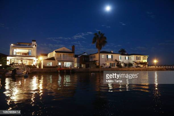 The moon rises above exclusive homes on Orange County's Balboa Island on October 20 2018 in Newport Beach California The threat of rising seas...