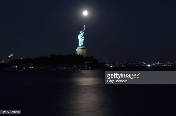 The moon rises above the Statue of Liberty in New York City one day before the full Harvest Moon on September 30 2020 as seen from Jersey City New...
