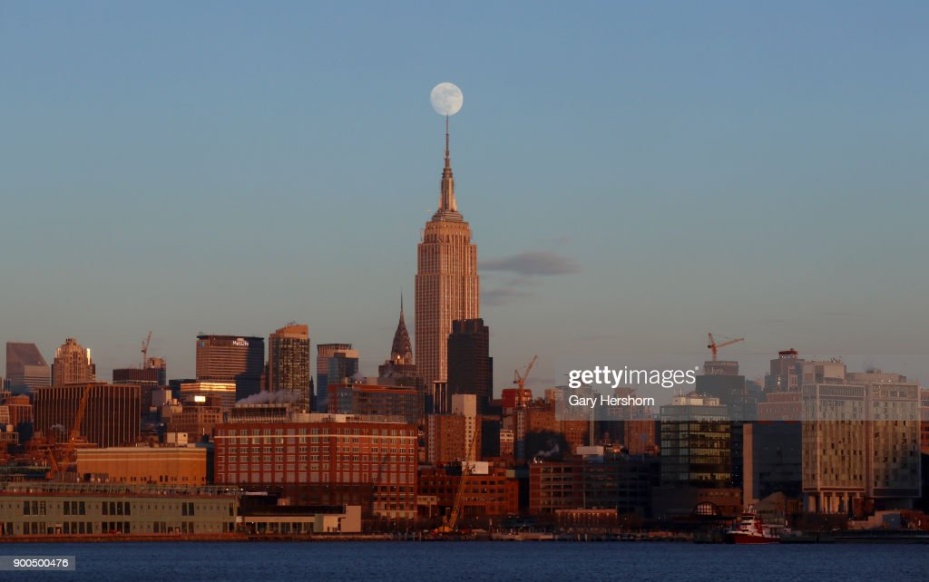 The Moon Rises At Sunset On New Years Eve Over The Skyline Of Midtown Manhattan And