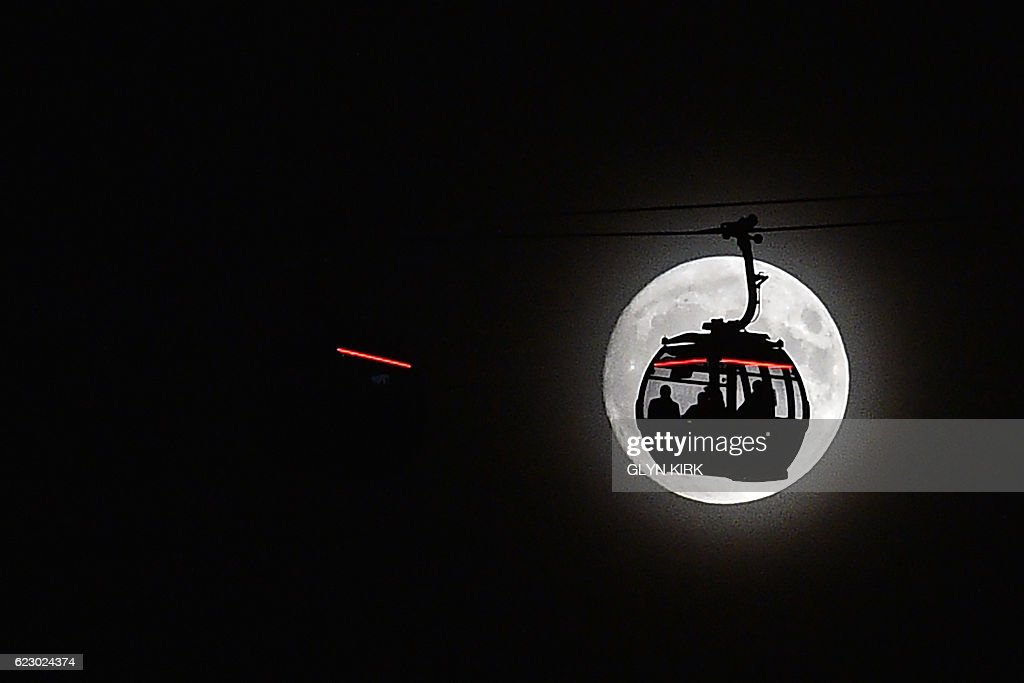 TOPSHOT - The moon rises behind a car on the The Emirates Air Line (cable car) in London's Docklands on November 13, 2016. Tomorrow, the moon will orbit closer to the earth than at any time since 1948, named a 'supermoon', it is defined by a Full or New moon coinciding with the moon's closest approach to the Earth. / AFP / Glyn KIRK
