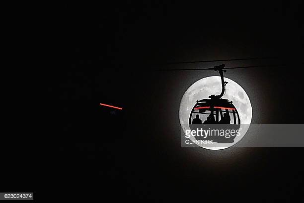 TOPSHOT The moon rises behind a car on the The Emirates Air Line in London's Docklands on November 13 2016 Tomorrow the moon will orbit closer to the...