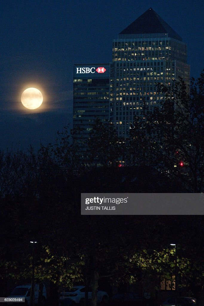The moon rises behind Canary Wharf in London on November 13, 2016. Tomorrow, the moon will orbit closer to the earth than at any time since 1948, named a 'supermoon', it is defined by a Full or New moon coinciding with the moon's closest approach to the Earth. / AFP / JUSTIN