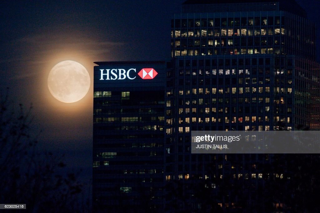 The moon rises behind HSBC bank in London's Docklands on November 13, 2016. Tomorrow, the moon will orbit closer to the earth than at any time since 1948, named a 'supermoon', it is defined by a Full or New moon coinciding with the moon's closest approach to the Earth. / AFP / JUSTIN