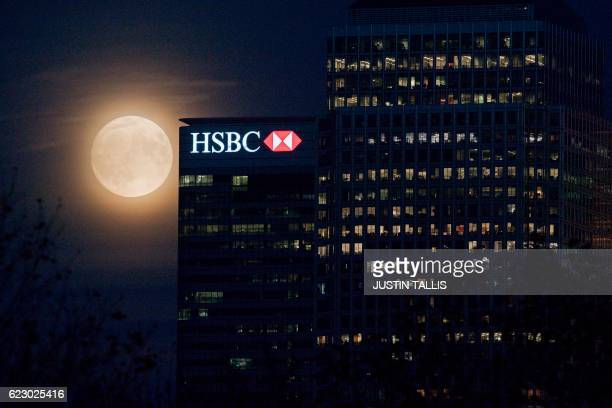 The moon rises behind HSBC bank in London's Docklands on November 13 2016 Tomorrow the moon will orbit closer to the earth than at any time since...