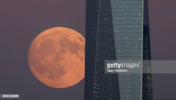 The moon rises behind One World Trade Center at sunset in New York City on October 4 as seen from Jersey City New Jersey