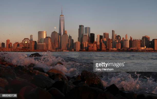 The moon rises behind One World Trade Center at sunset in New York City on December 1 as seen from Jersey City New Jersey