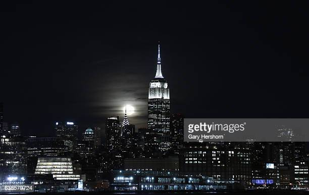 The moon rises behind the Empire State Building in New York City on January 13, 2017 as seen from Hoboken, NJ.