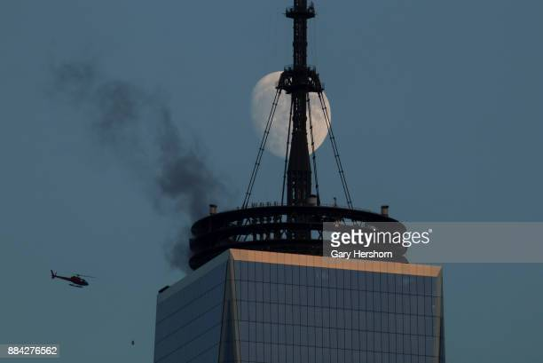 The moon rises behind the skyline of lower Manhattan at sunset in New York City on November 30 as seen from Jersey City New Jersey