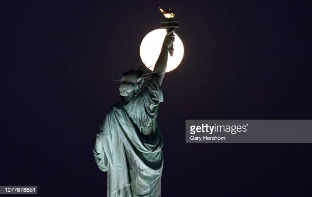 The moon rises behind the Statue of Liberty in New York City one day before the full Harvest Moon on September 30 2020 as seen from Jersey City New...