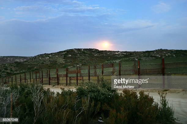 The moon rises behind the USMexico border fence as citizen volunteers carry out nightly patrols in search of illegal border crossers from Mexico on...
