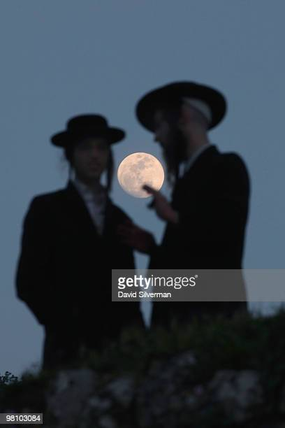 The moon rises behind ultraOrthodox Jews who gather to collect water in the Mayim Shelanu ritual to be used the following day to make matza the...