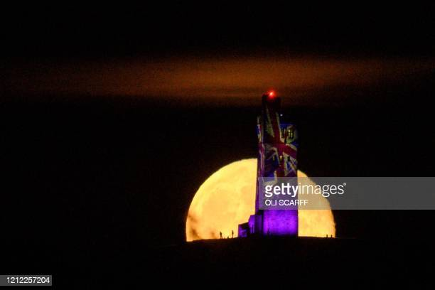 The moon rises behind Victoria Tower which has been illuminated with Union Flags to mark the 75th anniversary of VE Day on Castle Hill overlooking...