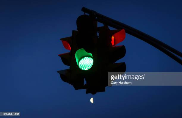 The moon rises below a traffic light at sunrise on March 9 2018 in Hoboken New Jersey