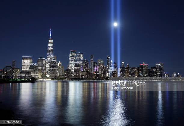 The moon rises between the beams of the Tribute in Light as it is tested over lower Manhattan and One World Trade Center in New York City on...