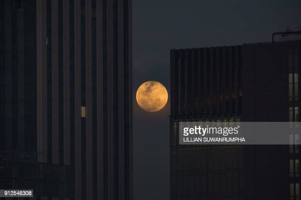 TOPSHOT The moon rises between two office buildings in Bangkok on January 31 2018 Skywatchers were hoping for a rare lunar eclipse that combines...