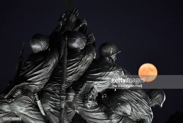 The moon rises near the Marine Corps War Memorial or the Iwo Jima Memorial on Sunday August 26 2018 in Arlington VA