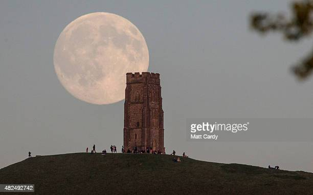 The moon rises over people gathered on Glastonbury Tor ahead of tomorrow's Blue Moon on July 30 2015 in Somerset England The full moon appearing on...