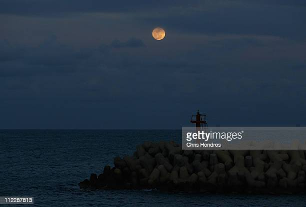 The moon rises over the harbor entrance April 17 2011 in the port in Misrata Libya Thousands of foreign workers and Libyans alike are trying to leave...