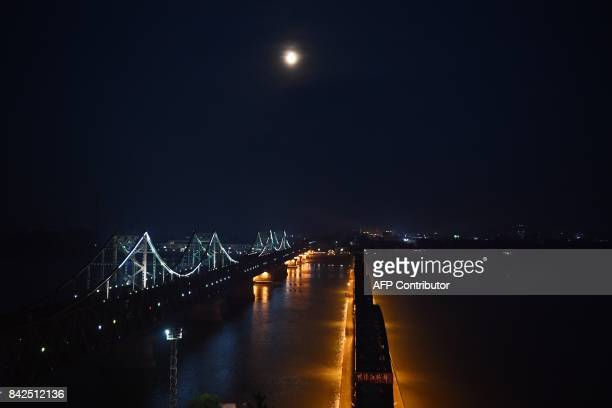 The moon rises over the North Korean town of Sinuiju behind the Friendship Bridge which connects Sinuiju and the the Chinese border city of Dandong...