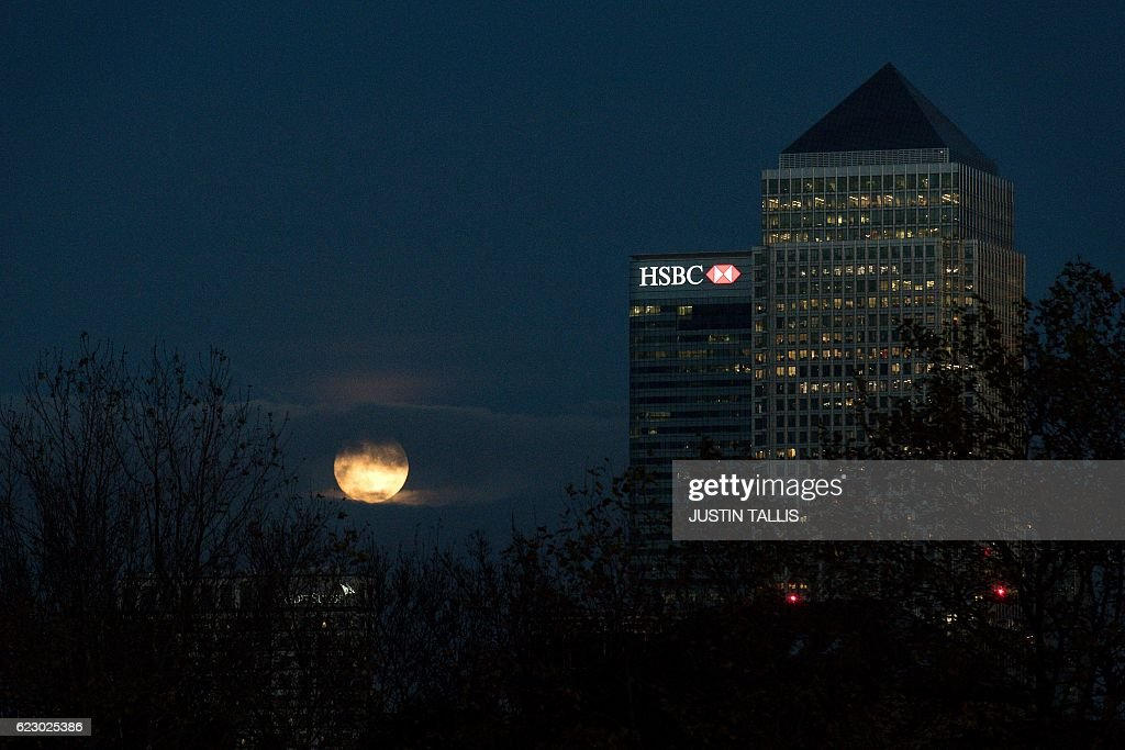 The moon rises through the clouds behind Canary Wharf in London on November 13, 2016. Tomorrow, the moon will orbit closer to the earth than at any time since 1948, named a 'supermoon', it is defined by a Full or New moon coinciding with the moon's closest approach to the Earth. / AFP / JUSTIN