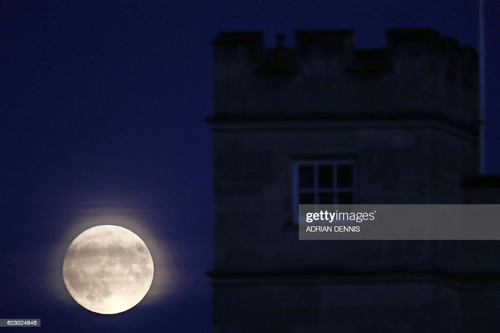 The moon rises with Syon House in the foreground, in west London on November 13, 2016. Tomorrow, the moon will orbit closer to the earth than at any time since 1948, named a 'supermoon', it is defined by a Full or New moon coinciding with the moon's closest approach to the Earth. / AFP / Adrian DENNIS