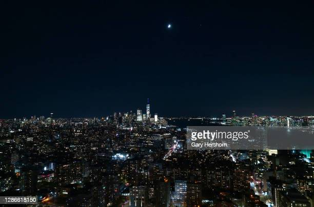 The moon, Saturn and Jupiter form a triangle as they rise over lower Manhattan and One World Trade Center after the sun set on November 19, 2020 in...