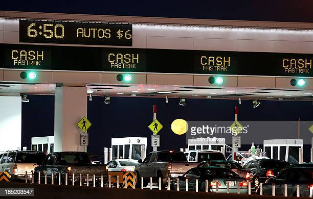 The moon sets as traffic backs up at the San FranciscoOakland Bay Bridge toll plaza while commuters make their way into San Francisco on the first...