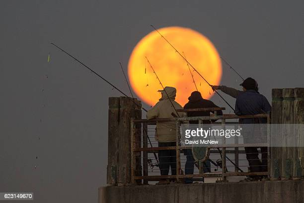 The moon sets behind people fishing on a pier during its closest orbit to the Earth since 1948 on November 14 2016 in Redondo Beach California The...