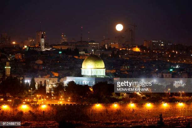 TOPSHOT The moon sets behind the city of Jerusalem early on January 31 2018 A cosmic event not seen in 36 years a rare 'super blood blue moon' may be...