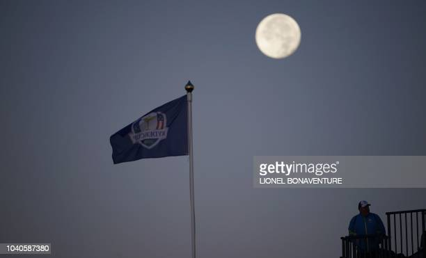 The moon sets behind the Ryder Cup flag as spectators look on before a practice session ahead of the 42nd Ryder Cup at Le Golf National Course at...